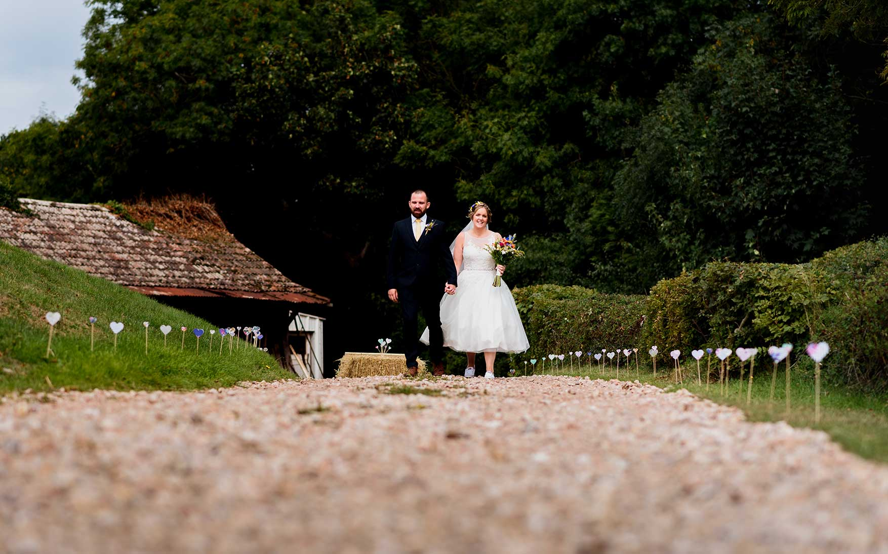 Bride and groom walking down path to the barn