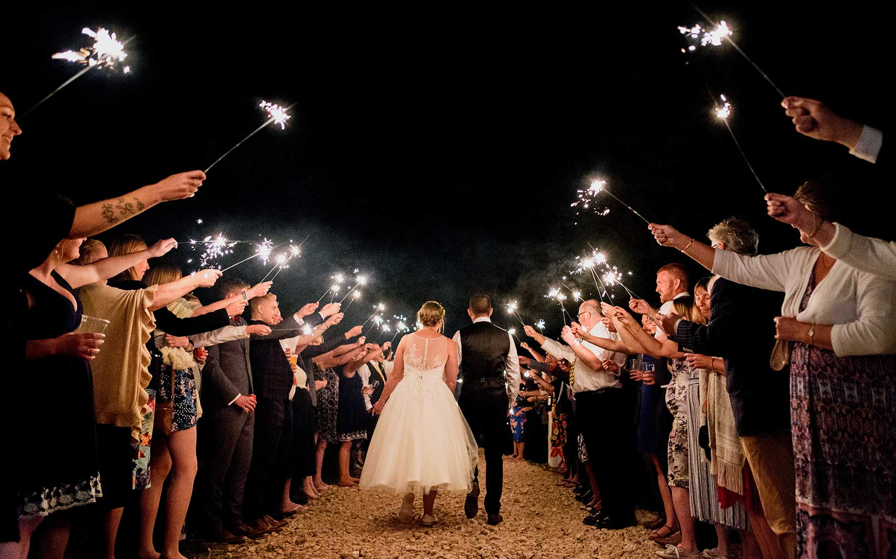 Guests hole up sparklers to salute the happy couple